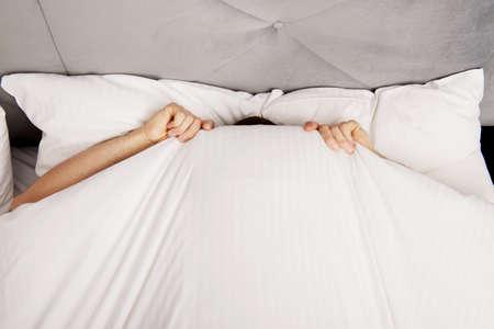 Grappige man verstopt in bed onder de lakens. Stockfoto