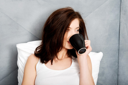 Beautiful woman drinking coffee in bed. photo