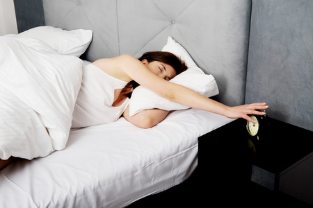 Tired and sleepy woman switches off alarm clock.