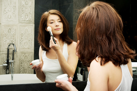 Beautiful woman doing make up in bathroom. Stock Photo