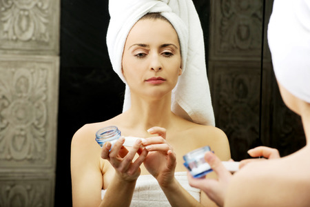 antiaging: Attractive woman putting anti-aging cream on her face.