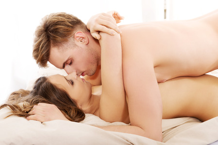 young couple sex: Young caucasian couple kissing on bed.