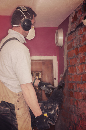 demolish: Adult repairman demolish wall in room.