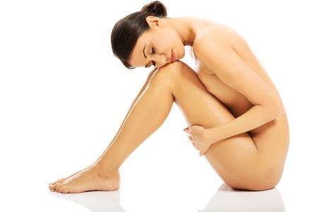 mujer desnuda sentada: Mujer desnuda delgado sentado con la cabeza en las rodillas.
