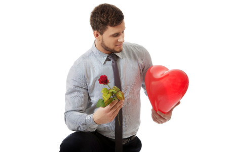 man kneeling: Young happy man kneeling with red rose and heart balloon.