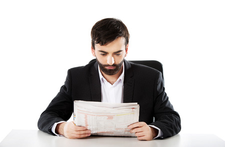 20 29: Young businessman reading newspaper in the office.