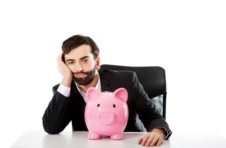 piggybank: Worried businessman with piggybank by a desk. Stock Photo