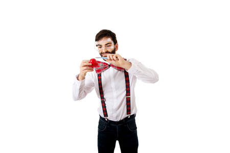 Funny man wearing suspenders cutting heart model with scalpel.. photo