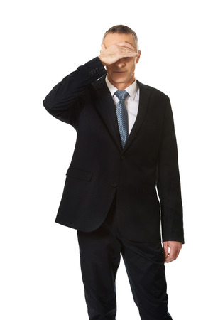embarassed: Mature embarassed businessman covering his face.