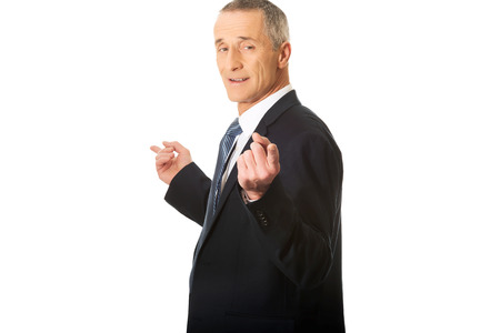 both: Mature businessman pointing with hands on both sides.