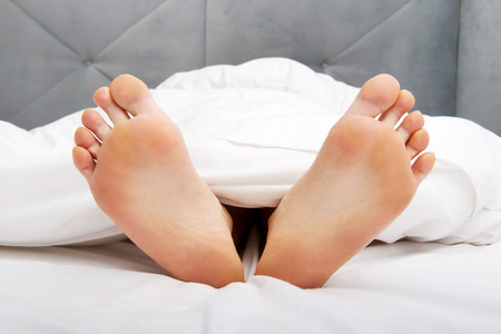 adult foot: Beautiful womans bare feet in bedroom. Stock Photo