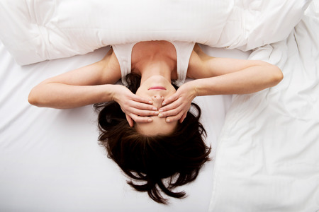 despertarse: Mujer morena Sleepy despertar y frotándose los ojos.