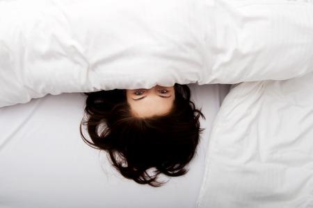 Het doen schrikken vrouw verbergen achter blad in bed.