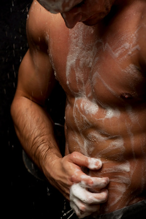 Handsome muscular man at the shower. Stock Photo