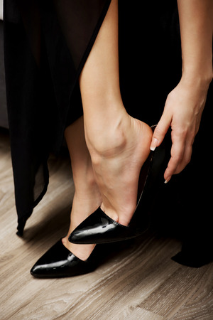 putting on: Beautiful woman putting on black high heels. Stock Photo