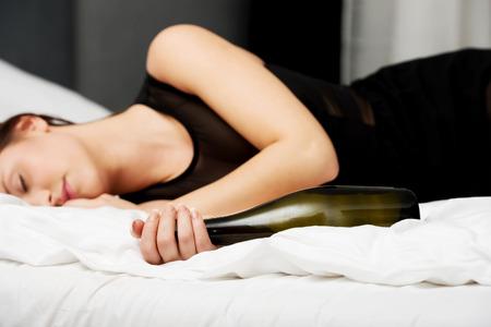 ebrio: Mujer borracha que duerme en la cama con una botella de vino. Foto de archivo