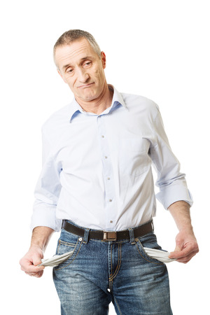 empty: Confused mature man showing his empty pockets. Stock Photo
