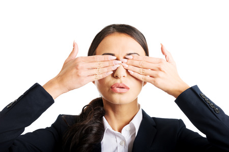 hands covering eyes: Portrait of young businesswoman covering eyes with hands.