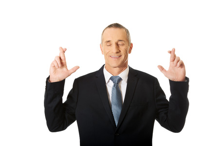 fingers crossed: Mature businessman making a wish with fingers crossed. Stock Photo