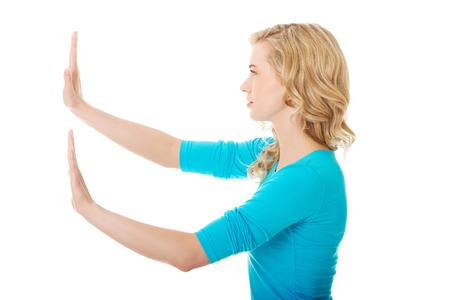 imaginary: Side view woman pulling imaginary screen. Stock Photo
