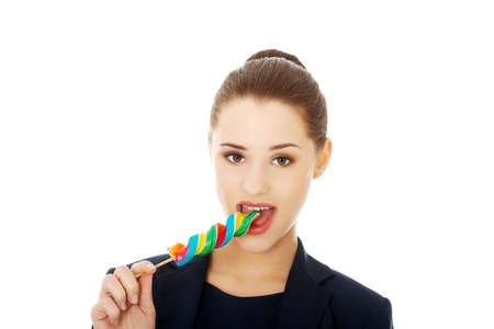 lolipop: Young happy businesswoman licking a lolipop