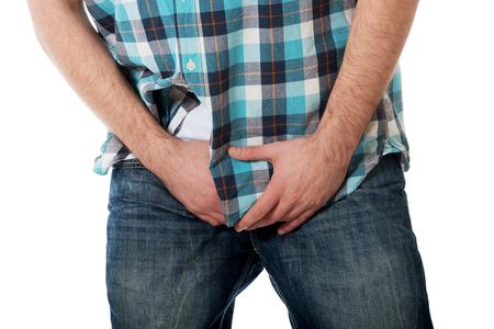 pene: Hombre joven que sostiene su entrepierna a causa del dolor.