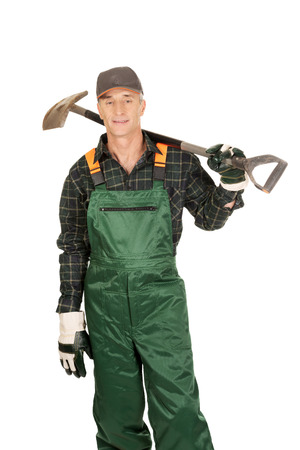 dibble: Smiling experienced gardener with a spade on shoulder Stock Photo