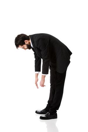 bending down: Apuesto hombre de negocios joven que agacharse.