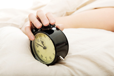 obudził: Exhausted man being awakened by an alarm clock in his bedroom.