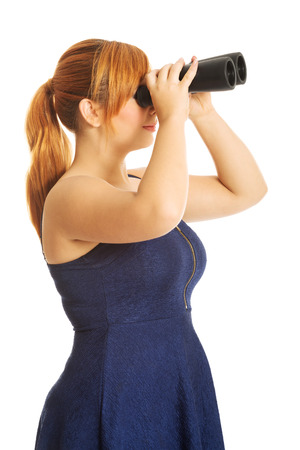Overweight woman looking through binoculars. photo