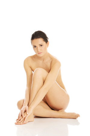 Slim nude woman sitting on the floor photo