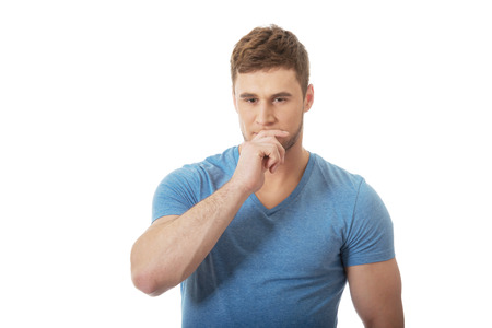 Young handsome pensive man with finger under chin. photo