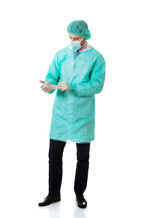 putting: Handsome male surgeon putting on protective gloves.