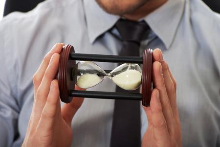 reloj de arena: Empresario la celebración de reloj de arena en la oficina.
