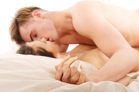 woman sex: Young caucasian couple kissing on bed.