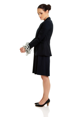 cuffed: Arrested businesswoman with handcuffs around hands.