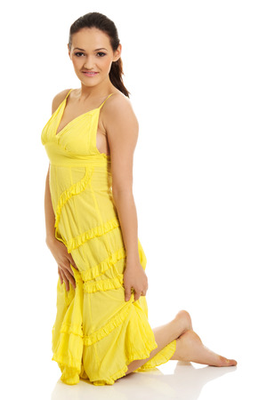 Beautiful woman sitting on knees in yellow summer dress. Stock Photo