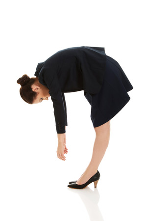 bending down: Joven mujer de negocios de flexi�n hacia abajo y mirando.