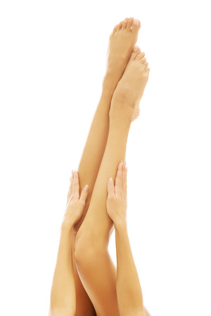 nude nature: Womans hands touching slim nude womans legs Stock Photo