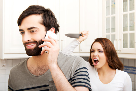 relationship breakup: Young rage woman hitting her talking partner with frying pan. Stock Photo