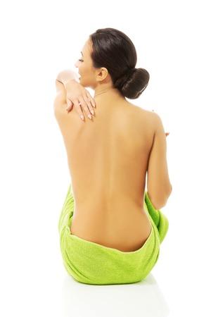 desnudo de mujer: Volver la vista mujer sentado envuelto en una toalla.