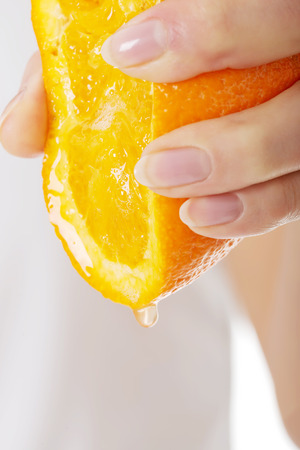 squeezing: Woman squeezing juice from an orange.