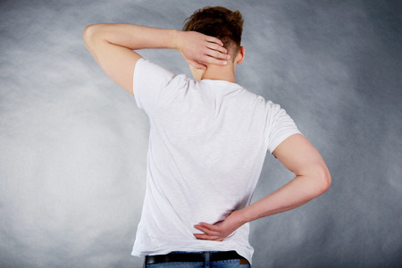 back  view: Young man suffering from neck pain. Stock Photo