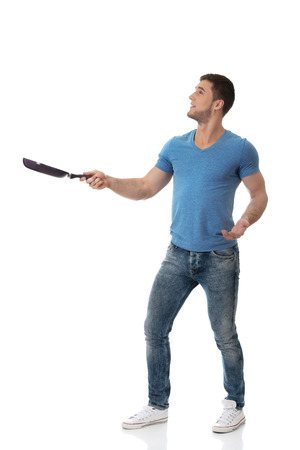 Handsome muscular man holding frying pan. Stock Photo