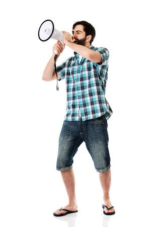 man yelling: Young man yelling into megaphone.