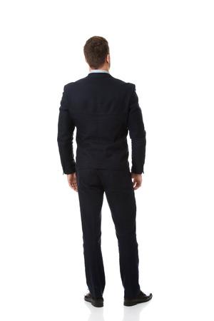 personas de espalda: Apuesto hombre de negocios de pie de nuevo a la cámara. Foto de archivo