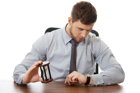 rushing hour: Businessman holding hourglass an checking time on his watch.