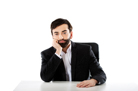 Thoughtful businessman sitting at the desk. photo