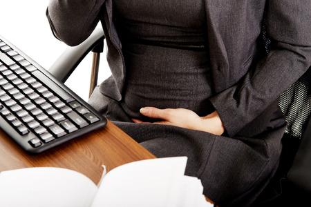 jeune fille: Une femme enceinte de toucher son ventre dans le bureau Banque d'images