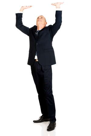 invisible: Full length businessman pushing invisible ceiling.